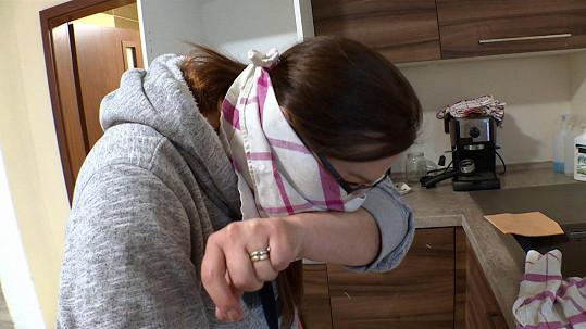 Při čištění trouby ji přepadly pocity na zvracení a nos si zakrývá utěrkou.