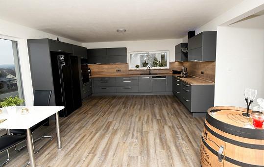 Kuchyně už je kompletní, laděná je do tmavých barev.