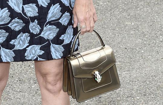 Mini šaty s rukávy sladila se šperky a kabelkou Bulgari.