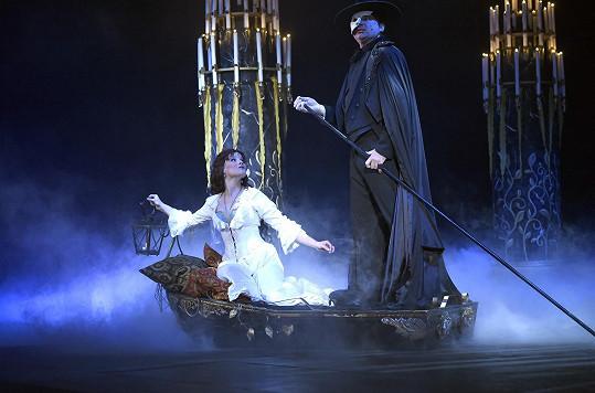 Marian jako Fantom opery na loďce na podzemním jezeře.