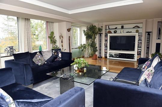 Obývací pokoj s obří televizí je místem pro relax u filmů.