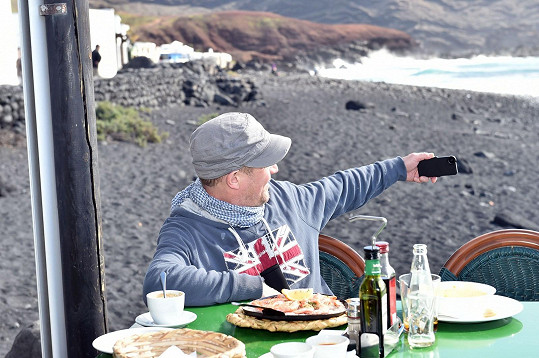 Na obědě v místní restauraci si vyfotil selfie s cedulí s názvem vesnice.