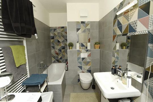 Koupelna je v šedých barvách a s moderním obkladem.
