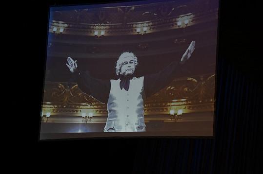 Na obrazovce se promítají fotky a ukázky z jeho slavných rolí.