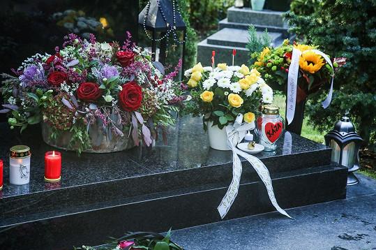 Lidé od časného rána chodí se svíčkami a květinami.