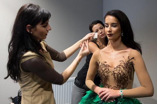 Na zkoušce jí do šatů obléká autorka modelu.