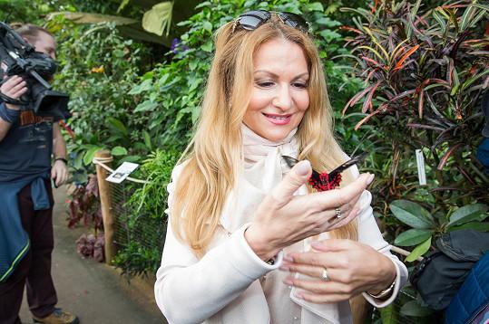 Herečka obdivuje exotické motýly na výstavě.