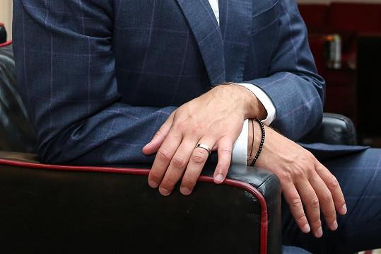 Hrdě nosí snubní prsten.