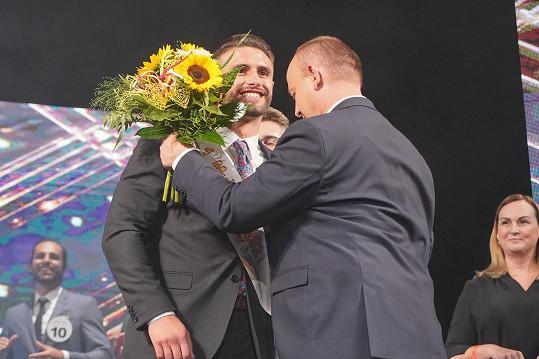 Prezident soutěže David Novotný nasazuje Lukášovi Vyšehradovi šerpu pro vítěze.