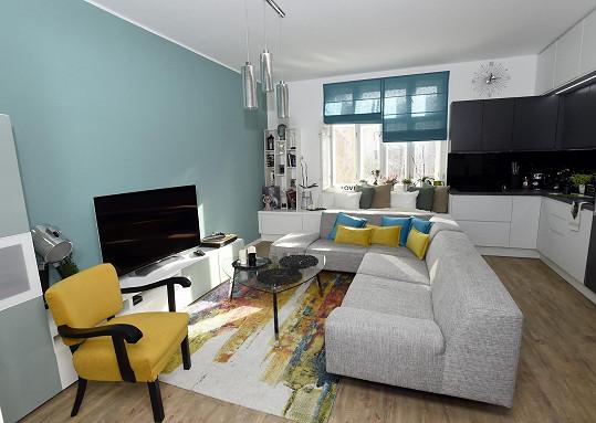 Největší místností bytu, kde bydlí známý tanečník necelý rok, je obývací pokoj s kuchyňskou linkou.