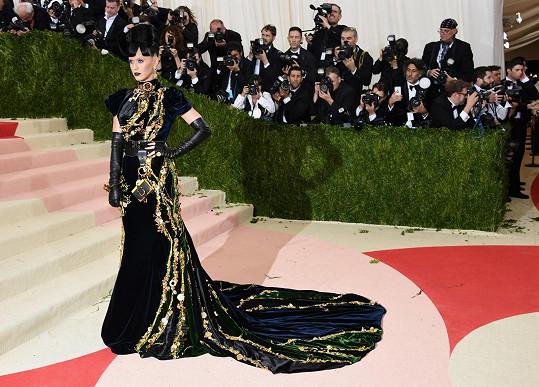"""Dlouhé sametové šaty vodstínech černé, půlnoční modři a smaragdově zelené sodhalenými zády a skoláží ze zlatých smaltovanýchvýšivek, zvýrazňujících díly sukňové části svlečkou. Dvojmo opásaný pas a náhrdelník typu """"obojek"""" zplexi želvoviny zdobily přívěsky ve stylu """"ztráty a nálezy""""."""