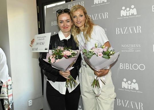 Modelka se s ředitelkou své nadace Terezií Sverdlinovou raduje z šeku. Výtěžek z prodeje limitovaných triček putoval na projekt Made BY Nadace Terezy Maxové dětem.