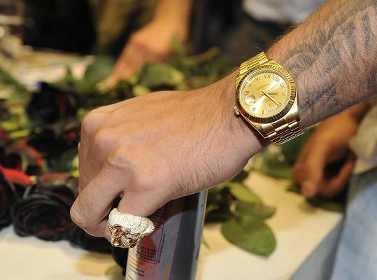 Nosí zlaté hodinky Rolex.