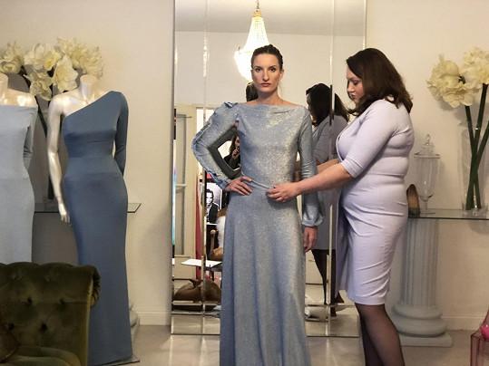Do materiálu šatů je vcelé ploše vetkaná stříbrná nitka, což umocňuje slavnostní dojem.