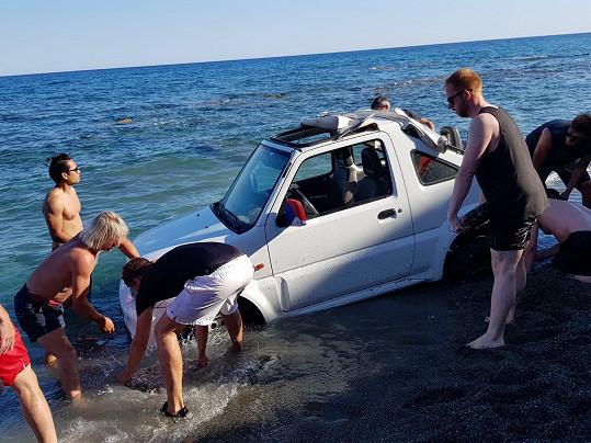 V patnácti lidech se jim nakonec podařilo auto z vody dostat.