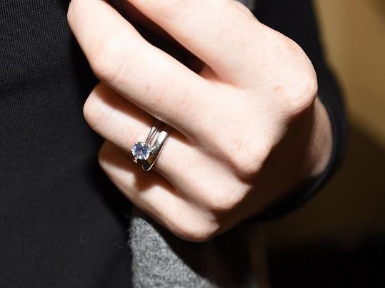 A ukázala snubní prsten.
