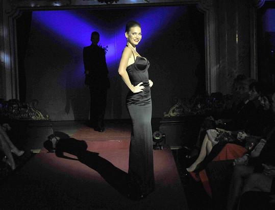 Andrea v dlouhé černé róbě s výstřihem vyztuženým kosticemi.