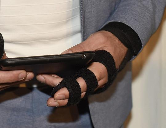 Herec musí mít na ruce ortézu, která mu drží prsty u sebe.
