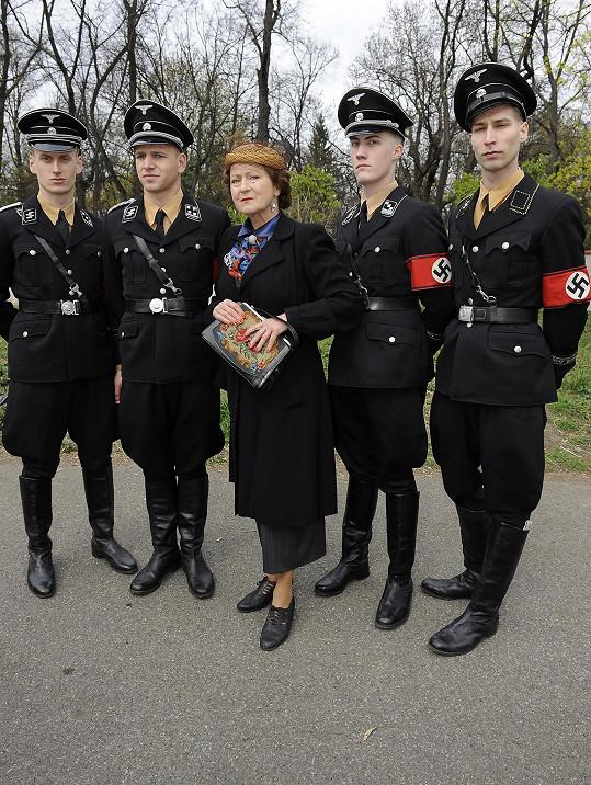 Oficiálnímu rozjezdu natáčení asistovali u vchodu Olšanských hřbitovů statisté v černých uniformách i nablýskané prvorepublikové mercedesky.