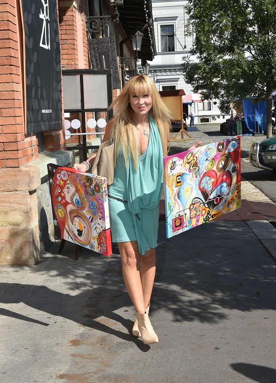 Kateřina Herčíková se svými obrazy. Na vernisáž se oblékla skromně.