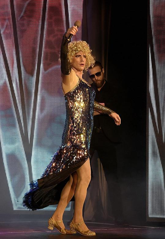 Tančí a zpívá v dámských šatech.