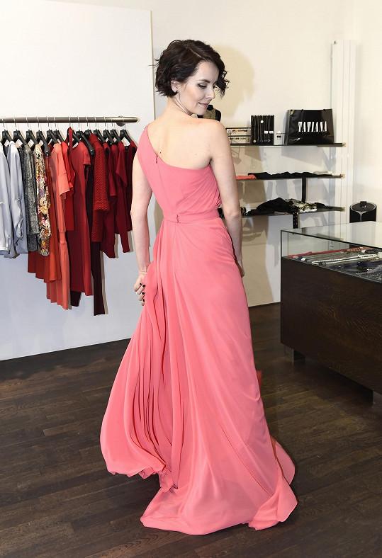 I růžové šaty na jedno rameno záda lehce odhalují.