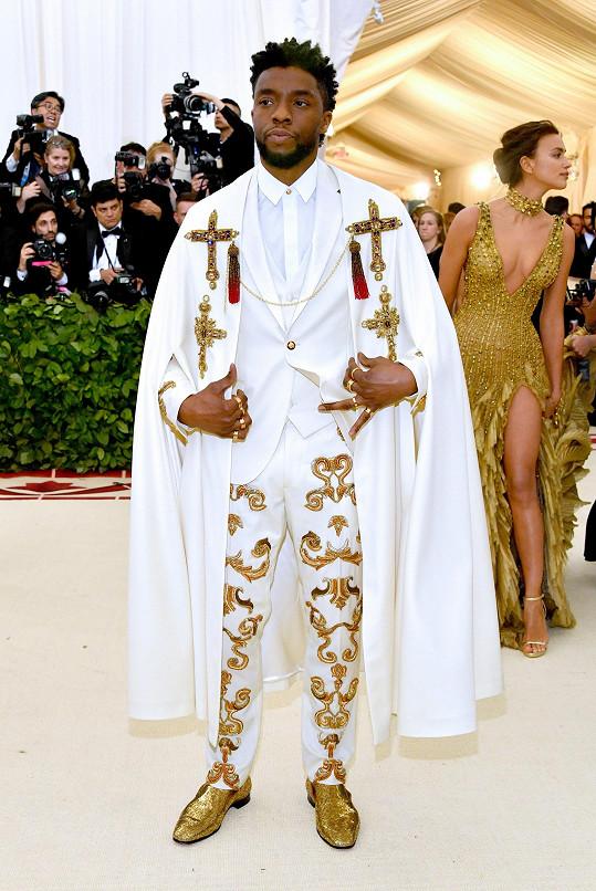Chadwick Boseman v krémovém modelu a pláštěnce od Versaceho s ozdobami v podobě zlatých křížů a výšivek s krystaly Swarovski