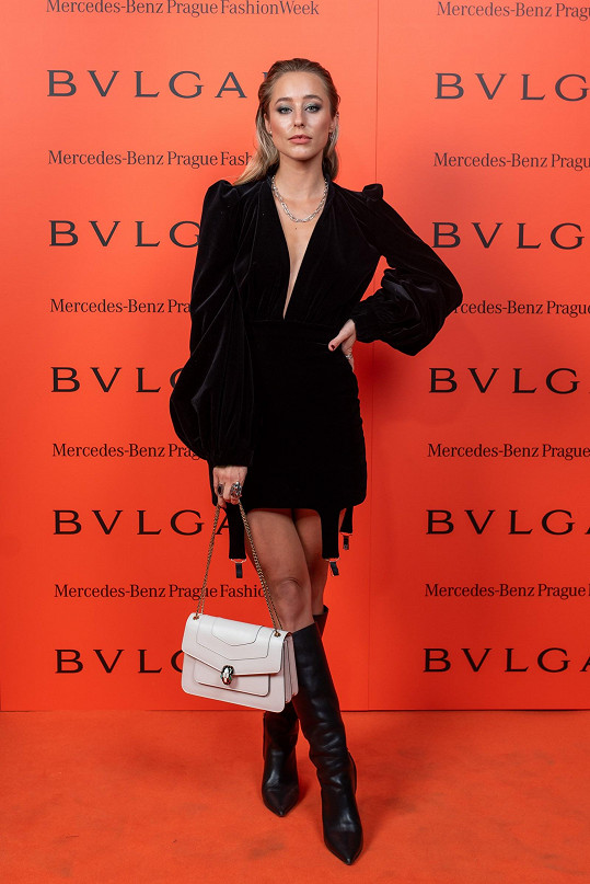 Módní influencerka Alex Sedláčková v šatech z černého sametu zvolila kontrastní bílou kabelku Bulgari na řetízku.
