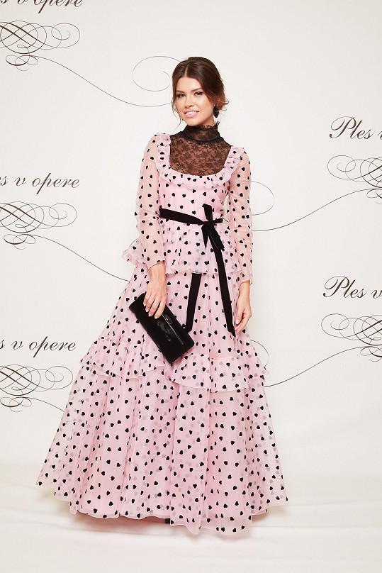 V loňské podzimní kolekci módního domu Valentino si Karolína Chomisteková vybrala tuto růžovou róbu s hravým potiskem srdíček. Šaty v retro střihu doplnila šperky od Lucie Šimončičové.