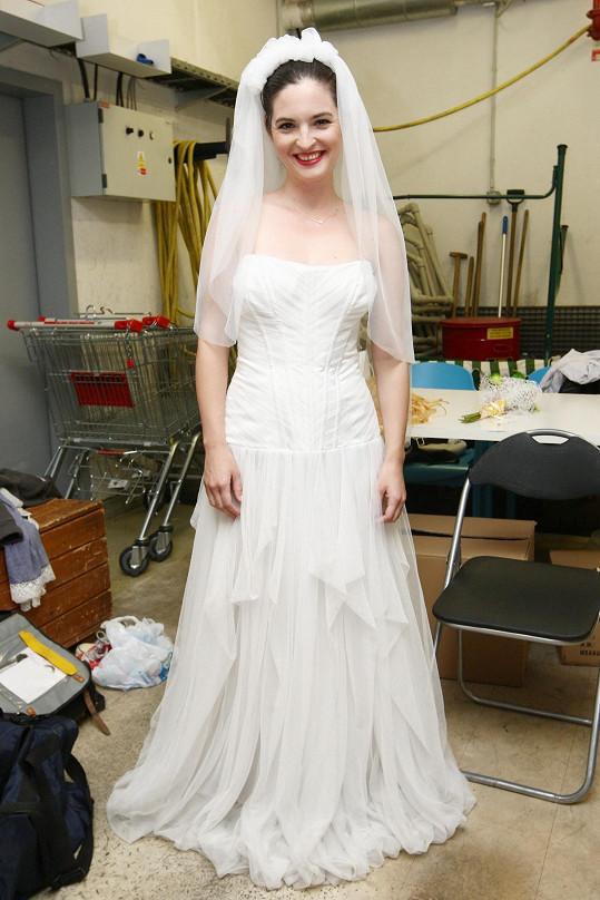 Svatební šaty jí sluší.