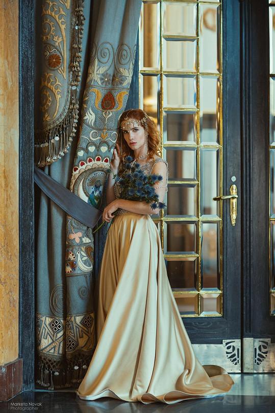 Herečku zdobila jemná čelenka a zlaté šaty.