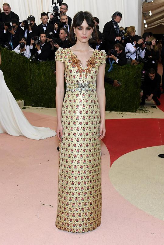 Francouzsko-britská herečka Stacy Martin měla na sobě dlouhé zlaté žakárové šatyMiu Miu s květinovým motivem a s brožemi zkrystalů,zdobícími ramena a výstřih. Nazula zelené semišové sandály stejné značky.