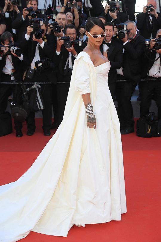 Rihanna má na sobě šaty a dlouhý plášť Dior Haute Couture z bílého hedvábného taftu. Chápu, že brýlemi Andy Wolf Eyewear chtěla popová diva rozbít vážnou scénu a přinést na francouzský festival trošku hollywoodské rebelie, ale mně tento doplněk připadá směšný.
