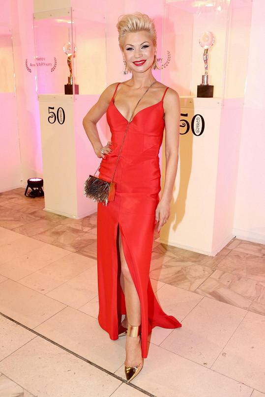 Návrhářka v šatech z červeného hedvábí z vlastní kolekce Yin Yang. Kabelka a boty pochází z limitovaná edice Jimmy Choo.
