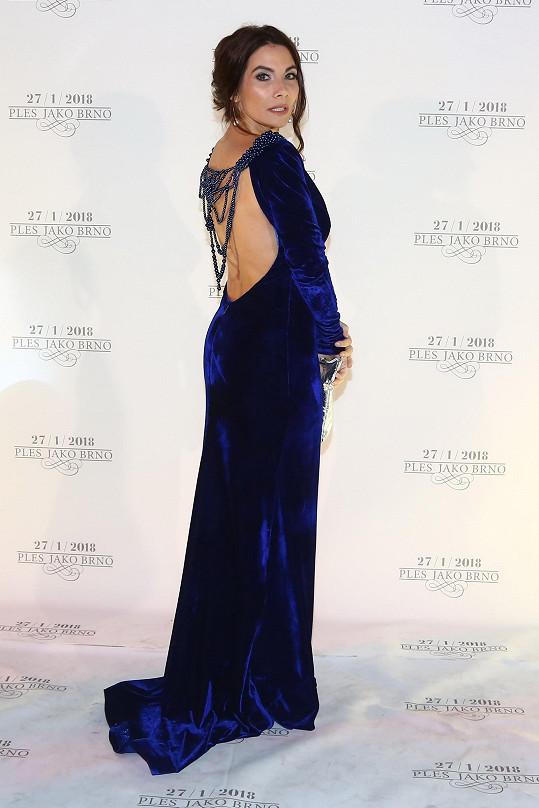 Eva Decastelo je malého vzrůstu a celistvý střih šatů s prodlouženou délkou jí opticky přidává centimetry. Šatům od Miriam Jansové z těžkého sametu dominoval výstřih zad s korálkovou aplikací.
