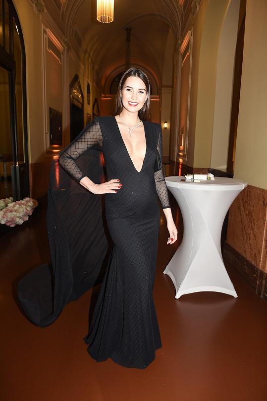 Modelka oblékla černé šaty s hlubokým výstřihem.