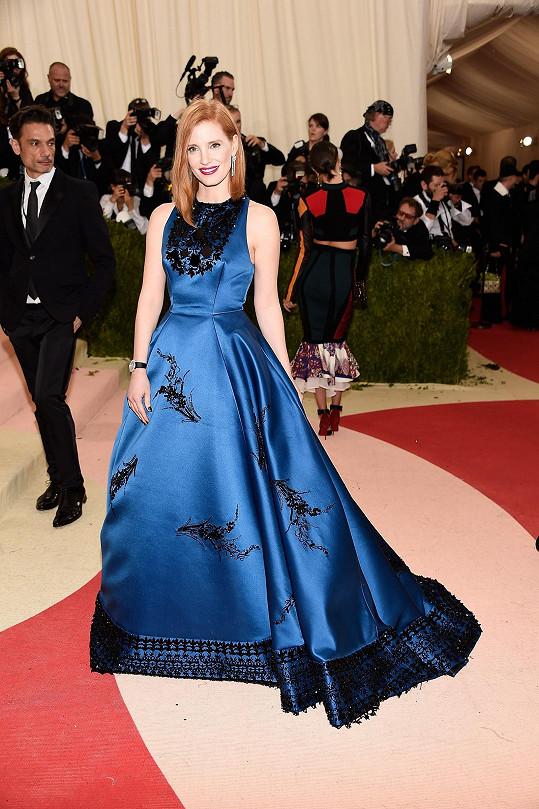 Úchvatná barva. Jessica Chastainměla na sobě dlouhé šaty Prada zhedvábného gabardénu vodstínu paví modři se strukturovaným korzetem a objemnou sukňovou částí, zdobené výšivkou sčernými krystaly skvětinovými a ornamentálními motivy a inspirované18. stoletím.