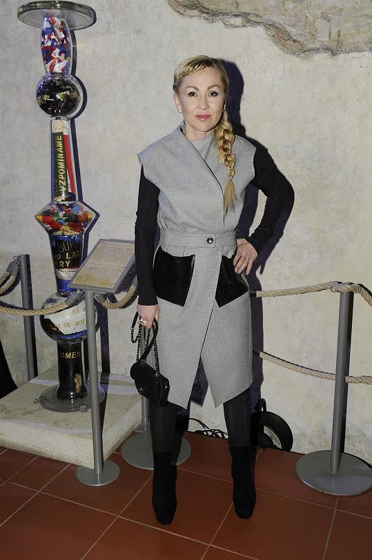 Namísto klasických šatů zvolila Kateřina Kaira Hrachovcová zavinovací kabát od Kateřiny Geislerové. Zpod něj vykukovaly elastické kalhoty od hereččiny další oblíbené návrhářky Denisy Nové. Minimalistickému celku vévodila ikonická kabelka Chanel.