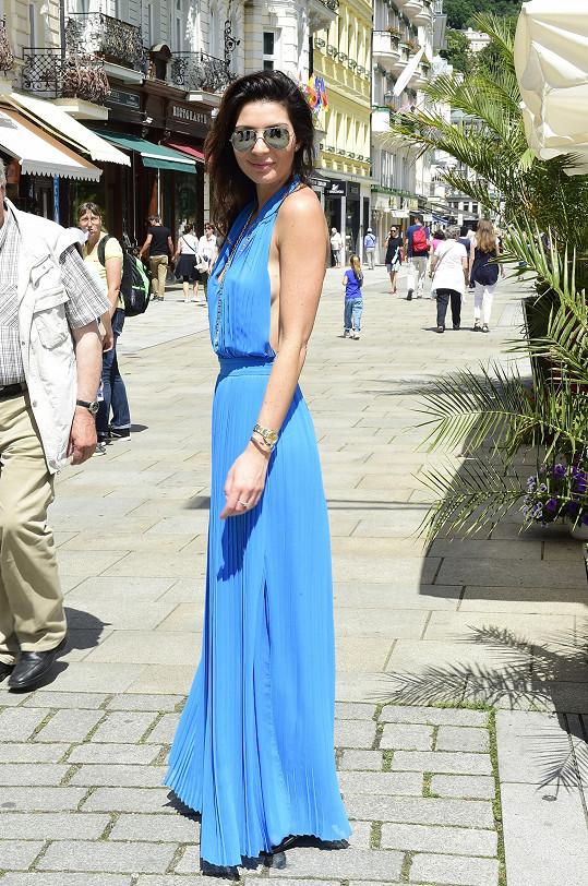Po promenádě v Karlových Varech se Monika prošla v plisovaných modrých šatech řecké návrhářky Charlotte Olympie. Ty doplnila kristuskami Balenciaga, pilotkami Ray-Ban a luxusní ikonickou kabelkou Chanel na řetízku.