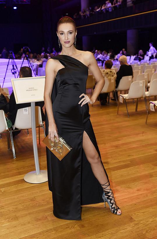 Modelce Taťáně Makarenko vytvořil asymetricky řešenou róbu na míru její dvorní návrhář Sam Dolce. Už tak výrazné šaty by snesly méně výrazné doplňky. Šněrovací střevíce a rozměrné psaníčko s aplikací jsou příliš.