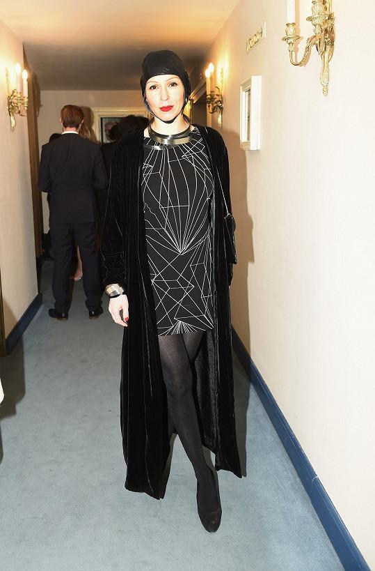 Přes černé vintage šaty s geometrickým vzorem, pořízené v New Yorku, přehodila Zuzana Stivínová sametový kabátek ve stejné barvě, navlékla černé matné punčochy, ozdobila se designovými šperky od Evy Eisler.