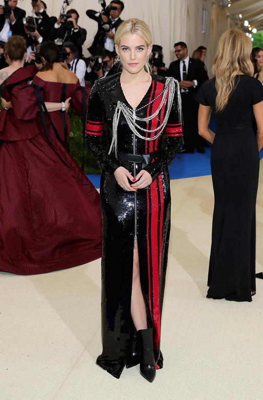 Styl Riley Keough je naprosto bezvadný. Herečka na sobě měla model Louis Vuitton se zipem v přední části, zdobený asymetricky loženými řetízky. Rudé pruhy inspirované vojenskou tematikou dodávají flitrovanému modelu šťávu.