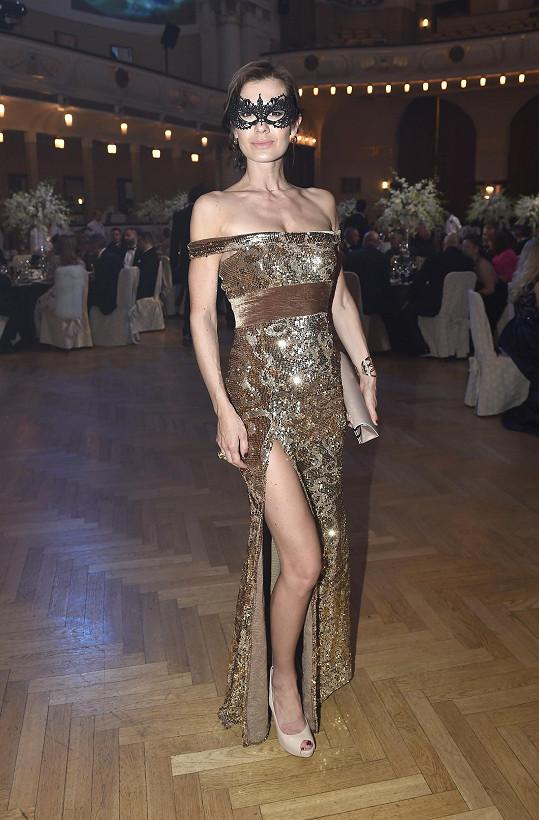 Jana Doleželová si pro tento večer vybrala šaty u Marty Musilové. Zlatou róbu sladila s kabelkou Guess a koktejlovým prstenem Roberto Coin.