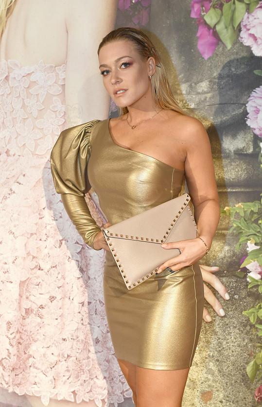 Blogerka v asymetrickém zlatém modelu.