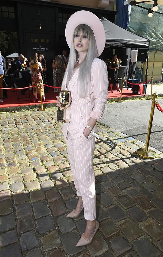 Na party ve stylu La Dolce Vita v růžovém kostýmu.