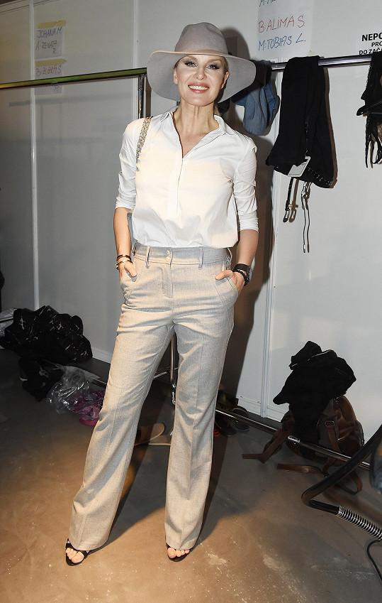 Na přehlídku své oblíbené designérky Kateřiny Geislerové oblékla Simona Krainová stylově návrhářčiny kousky. Podle návrhu Geislerové je i klobouk inspirovaný městem, který byl navržen pro značku Tonak.