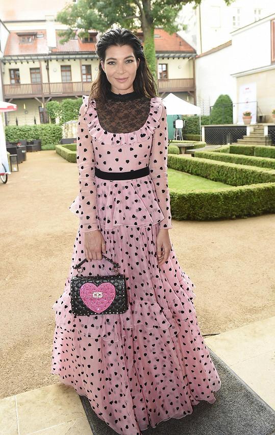 Výrazné šaty doplnila výraznou kabelkou - spojoval je symbol srdce.