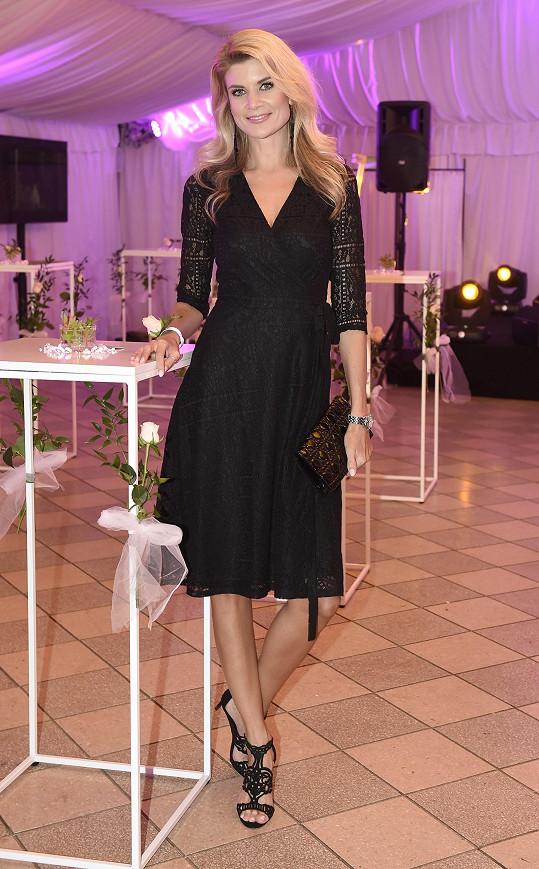Decentní černé šaty s nepříliš hlubokým výstřihem a delšími rukávy z dílny Poner se odvážila Iveta Vítová doplnit černým psaníčkem Dior se vzorem cannage a obutím, které stejně jako šaty zdobil vzorek krajky. Nepůsobilo to ale vůbec přeplácaně.