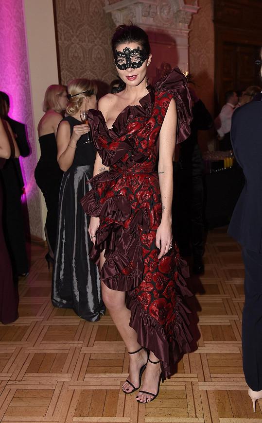 Na maškarní bál oblékla model od Vivienne Westwood. Od věhlasné módní návrhářky oblékla korzetové šaty v bordó provedení, které doladila psaníčkem Nancy Gonzalez. Nezapomněla na škrabošku.