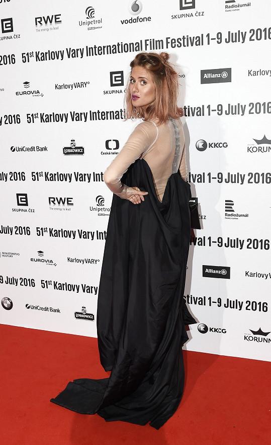 Emma Smetana ještě není omezena těhotenstvím, neboť se jí těhotenské bříško zatím neklene. I tak ale zpěvačka zvolila volné šaty áčkového střihu od Hany Zárubové, které naprosto vyhovují jejímu stylu. Vzdušný model doplnila psaníčkem Leeda.